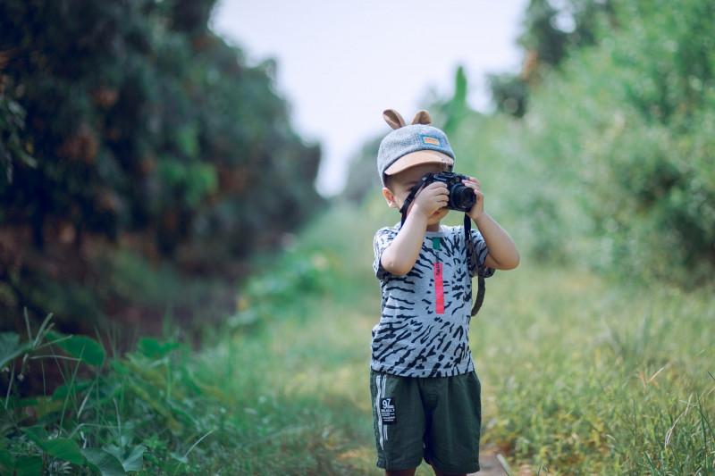 boy-using-camera-near-green-leaf-plants-1374510