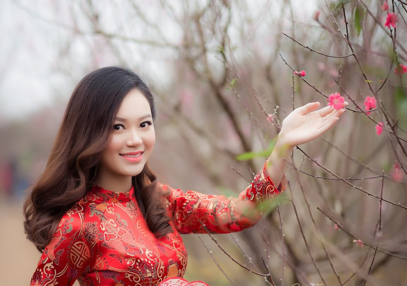 woman-wearing-red-long-sleeved-dress-holding-pink-petaled-807842